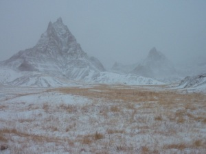 Blowing snow obscures the steep formations of Badlands