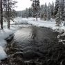 snow-covered trees and ground contrast with the dark waters of the Firehole River at Old Faithful