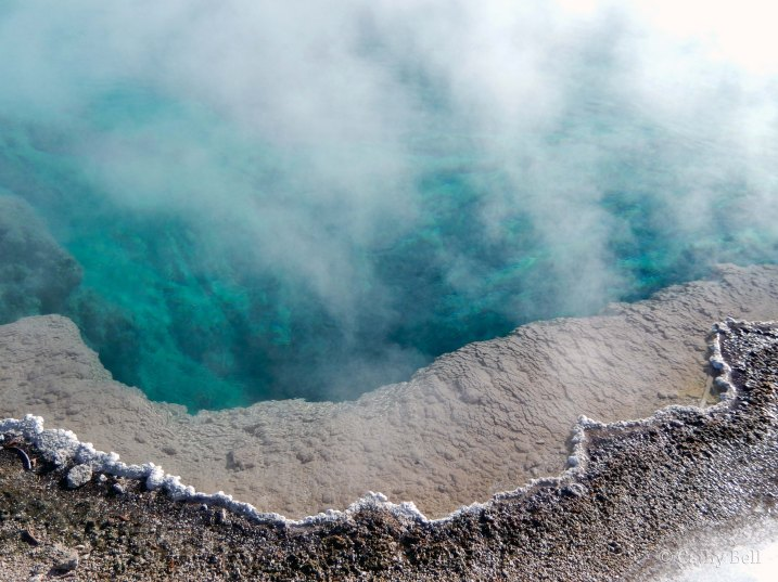 blue-green waters of a hot spring steam in the cold air